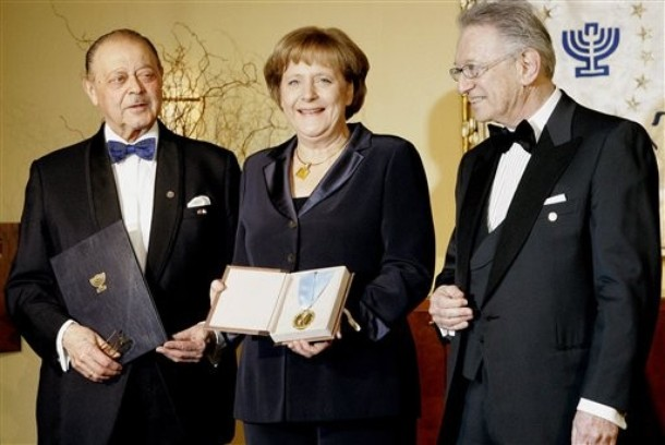 "German Chancellor Angela Merkel, center, smiles as she is awarded with the ""B'nai B'rith Europe Award of Merit"" in the German capital Berlin Tuesday, March 11, 2008. Jewish organization B'nai B'rith honored Merkel for her engagement in fighting anti-semitism and racism. At left stands B'nai B'rith President Reinold Simon, and at right, Honorary President Joseph Domberger. (AP Photo/Fritz Reiss)"